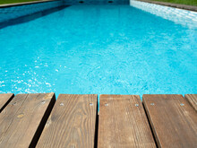 Ripped Wavy Water Surface In Swimming Pool With Wooden, Old Deck And Green Grass Around. Swimming Pool Area In Hotel Or Villa. Summer Vacation Background.