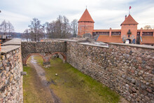Trakai, Lithuania - February 16, 2020: Medieval Gothic Island Castle With Stone Walls And Towers With Red Tiled Roofs. Trakai Castle Is One Of The Most Popular Tourist Destinations In Lithuania