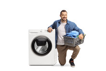 Smiling Young Man Kneeling Next To A Washing Machine And Holding A Loundry Basket
