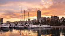 Alicante Harbor With Luxury Yachts And Sailboats, Promenade Palm Trees In Old Town At Sunset, Spain. Beautiful View Of Touristic Town Port In Costa Blanca Region On Mediterranean Sea Coast.