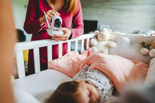 Unknown Caucasian Woman Mother Adjusting And Setting Up Surveillance Security Camera On Baby Bed At Home In Bedroom Watching Small Child In Cradle While Sleeping In Room In Day Motherhood Care Concept