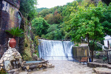 Man-made Waterfall In The City Of New Athos. Attraction In The City Park. The Dam. Water Falls From A Height.