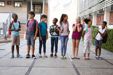Group Of Diverse Students With Backpacks Smiling While Looking At Each Other At School