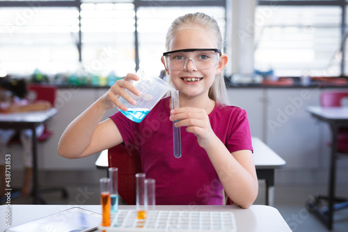 Caucasian girl pouring chemical from beaker into test tube in science class at laboratory