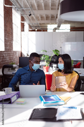 Diverse male and female colleague in face masks sitting at desk discussing, using laptop and tablet