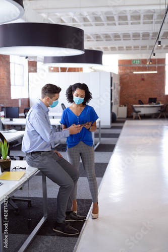 Diverse male and female colleague in face masks looking at tablet and discussing standing in office