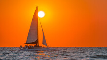 Sailboat. Beautiful Seascape With Sail Boat Or Luxury Yacht On Horizon. Ocean Sunset And Red Sky. Summer Vacation In Florida. Good For Travel Agency, Billboard Or Post Card. Photo With Copy Space.