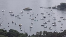 Boats Anchored In Place And Ferry Boat Approaches Dock