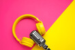 Leinwandbild Motiv Retro microphone with headphones on color background