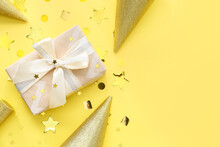 Gift Box With Party Hats And Confetti On Color Background