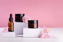 Amber Glass Containers For Cosmetics Produce - Creams, Essential Oil  Standing On White Podiums With Spring Flowers. Template For Branding Identity For Cosmetics Produce.