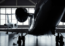 Luxury Private Jet Plane Storage Inside The Hangar. Natural Black And White High Contrast.