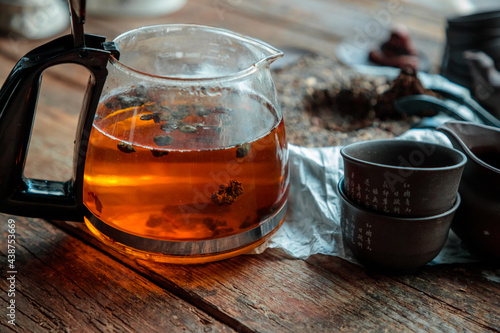 Fotografiet modern glass kettle with brewing on an old wooden table