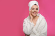 Leinwandbild Motiv Happy young woman in bathrobe with towel on head against pink background, space for text. Washing hair