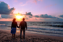 Seascape In The Evening. Young Couple Stands On The Beach In The Evening And Looks At The Beautiful Sunset