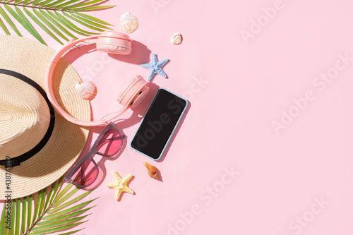Summer backdrop with sedge hat, laptop, phone and palm leaf on pink background Fototapeta