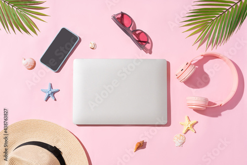 Fotografia Summer backdrop with sedge hat, laptop, phone and palm leaf on pink background