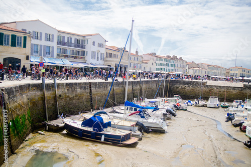 Fotografía View on the harbor of Saint-Martin-de-Ré at lowtide with boats and people walkin