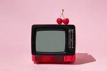 Creative Layout With Old Tv And Bright Red Cherry On Pastel Pink Background. Retro Style Aesthetic Idea. Vintage Television And Summer Fruit Concept.