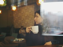 A Young Woman Walks Along The River In Autumn, And Then Warms Herself With Hot Tea In A Cafe