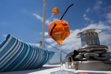 Aperol Spritz Cocktail Drink On The Boat Deck Next To Pillow And Anchor Windlass Of The Sailing Catamaran Yacht