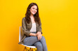 Portrait of attractive confident cheerful girl sitting on chair isolated over vibrant yellow color background