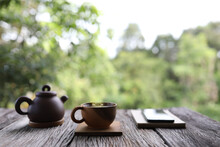 Wooden Tea Cup With Teapot And Notebook And Phone On Wooden Table