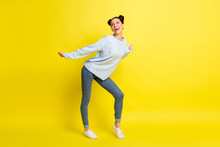 Photo Of Dream Lady Dance Open Mouth Look Empty Space Wear Blue Sweater Jeans Sneakers Isolated Yellow Background