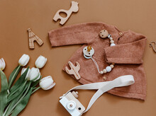 Flat Lay Composition With Tulips, Girl Knitted Jacket And Wooden Camera. Newborn Clothes, Baby Staff, Baby Shower. Top View, Flat Lay