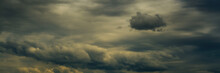Wide Panoramic View Of The Dark Opaque Dramatic Stormy Sky With Dense Cumulus Clouds And Atmospheric Haze. Artistic Moody Cloudscape