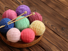 Colorful Yarn Balls And Knitting Needles In Basket On Wooden Background
