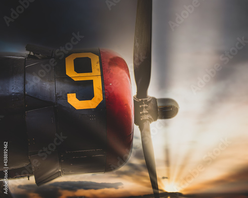 Fotografiet Vintage World War Two bomber airplane engine and propeller Sun low in the sky