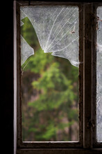 Broken Old Window With Glass And Forest In The Background.