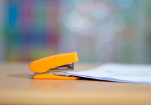 An Orange Stapler That Sits On The Desk Ready For Stapling The Papers In A Series Of Arrangements.