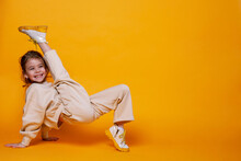 Cute Little Girl Dancing On A Yellow Background. Space For Text.