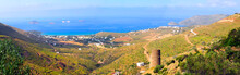Panoramic View Of The Bay Of Gavrio On The Island Of Andros, Famous Island Of The Cyclades, With In The Foreground The Agios Petros Tower, The Construction Of Which Dates From The 4th Century BC