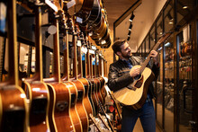 Talented Caucasian Musician In Leather Jacket Checking The Sound Of New Guitar Instrument In Music Shop.