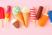 Variety Of Colorful Summer Popsicles And Ice Cream Treats. Overhead View Scattered On A Pink Background.