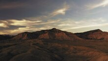 Aerial Flight Toward Huge Desert Mountains With Dramatic Sunset Clouds