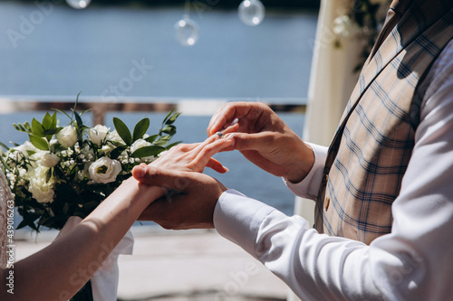 The bride and groom put on each other wedding rings Fotobehang