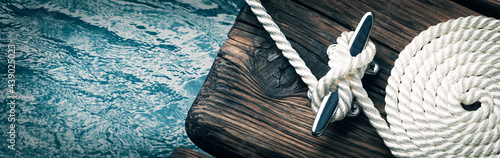 Fotografiet Close-up Of Coiled Boat Rope Secured To Cleat On Wooden Dock