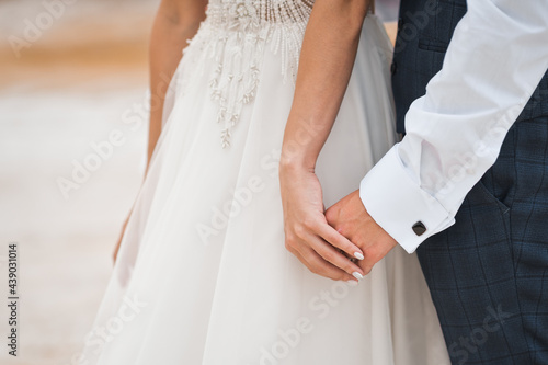The bride and groom carefully and tenderly hold hands 2759. Fotobehang