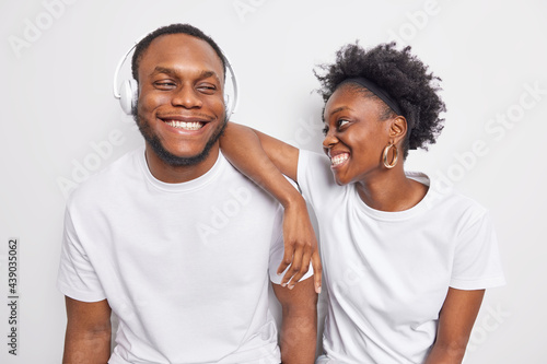 Valokuvatapetti Happy positive friendly Afro American teenage woman and man smile gladfully dressed in basic casual t shirts have good mood listen favorite music isolated over white background
