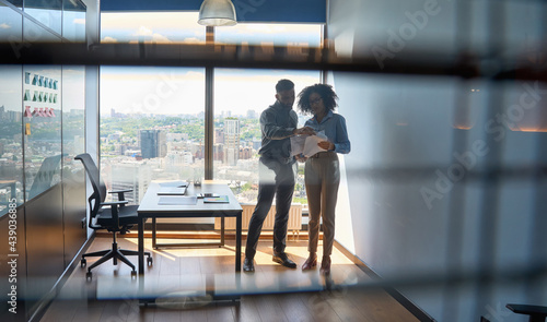 Fotografie, Obraz Indian ceo advisor male boss mentor explaining financial analytics report to African American female intern holding paper documents standing in modern office
