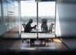 Leinwandbild Motiv Young indian businessman ceo hr director having interview hiring for job with female African American attorney sitting in office at panoramic view window. Shot through jalousie glass.