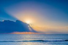 USA, Florida, Boca Raton, Sun Rising Behind Clouds Above Sea