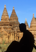 Myanmar, Bagan, Mandalay Division, Silhouette Of Young Woman Sitting In Front Of Buddhist Pagodas