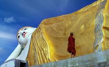 Myanmar, Monyma, Mandalay District, Novice Monk Praying Under Giant Statue Of Reclining Buddha In Lay Kyune Sakkyar Temple
