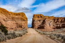 USA, Utah, Escalane, Dirt Road Between Sandstone Cliffs In Grand Staircase-Escalante National Monument