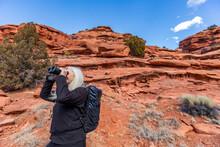 USA, Utah, Escalante, Senior Woman Uses Binoculars While Hiking In Grand Staircase-Escalante National Monument